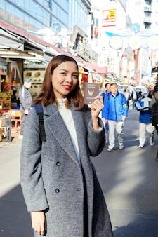 Aziatische vrouwen die paspoort in stad houden