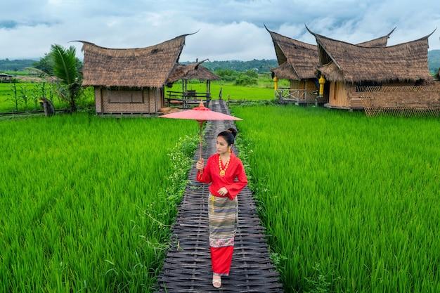 Aziatische vrouwen die traditioneel thais kledingskostuum dragen volgens de thaise cultuur op de beroemde plaats in de provincie nan, thailand