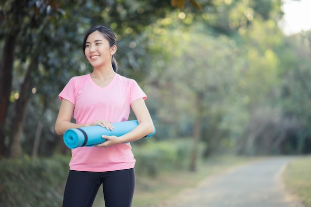 Aziatische vrouwen die yogamatten vasthouden, gaan yoga doen in het park om gezond te blijven en een goede conditie te hebben.