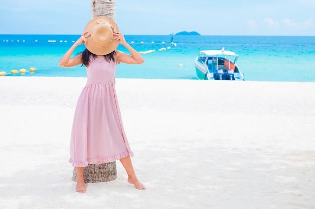 Aziatische vrouwen die zich op overzees strand met roze kleding bevinden zij gelukkig van openluchtzomer op zandstrand met blauwe lucht en de zee