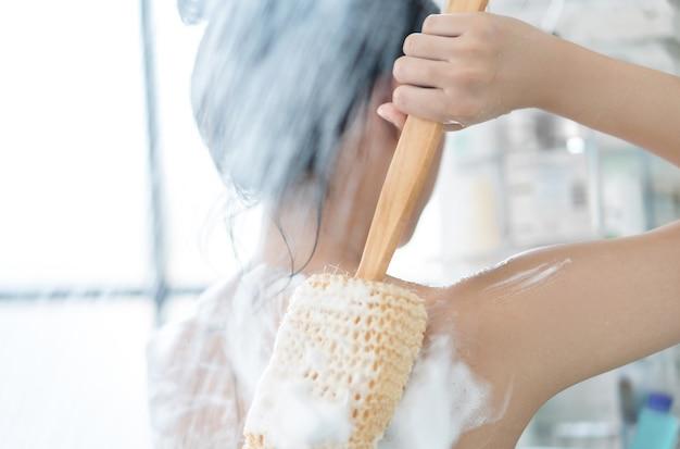 Aziatische vrouwen douchen in de badkamer waarin ze zeep wrijft, ze wrijft over haar rug