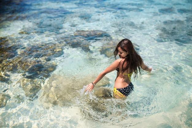 Aziatische vrouwen dragen bikini's die spelen in de zee