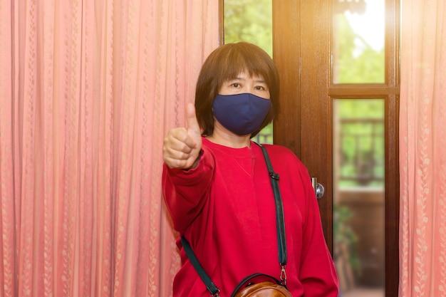 Aziatische vrouwen dragen een chirurgisch masker of gezichtsmasker voordat ze het huis verlaten om de infectie van covid-19 te verminderen