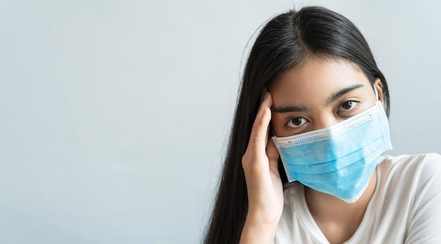 Aziatische vrouwen dragen een masker en houden hun hoofd vast vanwege hoofdpijn. ze heeft koorts en migraine door stress of laat slapen, weinig slaap, onvoldoende rust in een gezond concept met kopie ruimte.