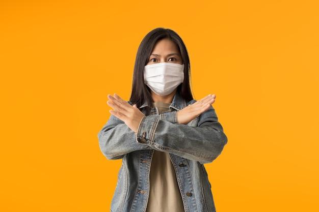 Aziatische vrouwen dragen een medisch gezichtsmasker met gekruiste handen die nee zeggen, geïsoleerd op een gele achtergrond