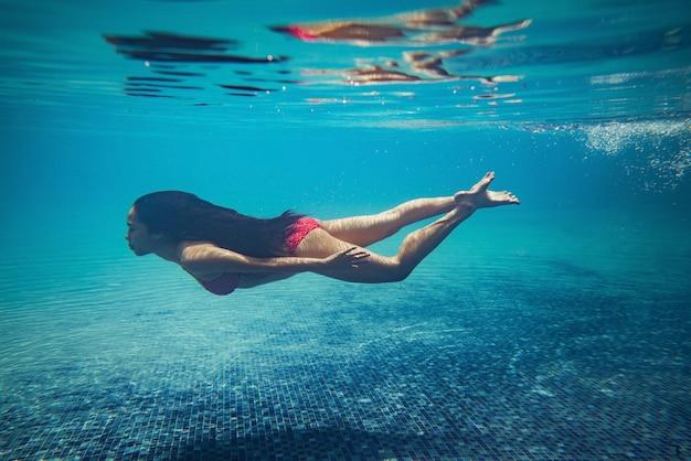 Aziatische vrouwen duiken bij het zwembad.