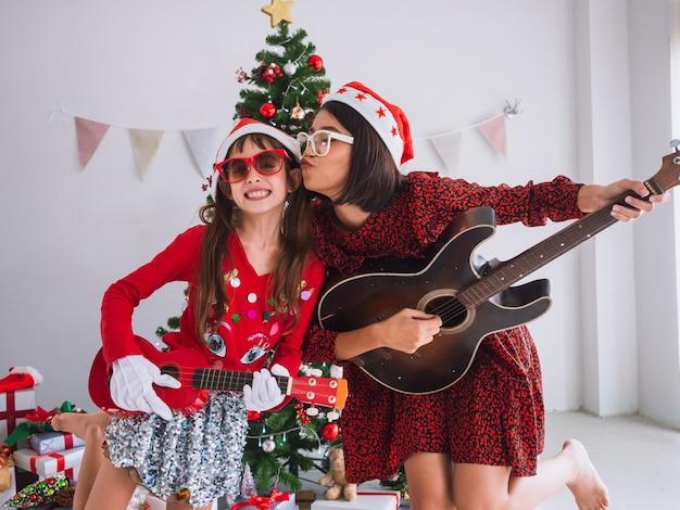 Aziatische vrouwen en kinderen vieren kerstmis door de gitaar binnenshuis te tokkelen. een meisje speelt een lied met een glimlach op eerste kerstdag