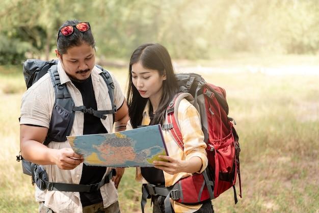 Aziatische vrouwen en mannen zijn backpackers. op zoek naar een kaart om te plannen om in het bos te kamperen.