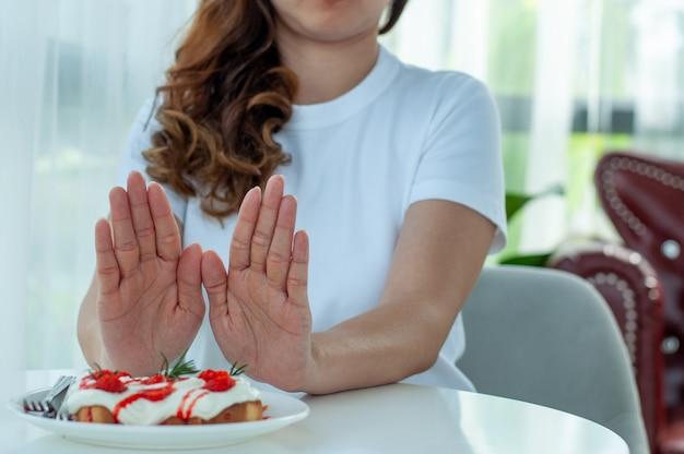 Aziatische vrouwen gebruiken beide handen om het dessertbord te duwen. afnemende voedingsmiddelen die zoet zijn. richtlijnen voor gewichtsverlies. kies om te raden wat goed is voor het lichaam.