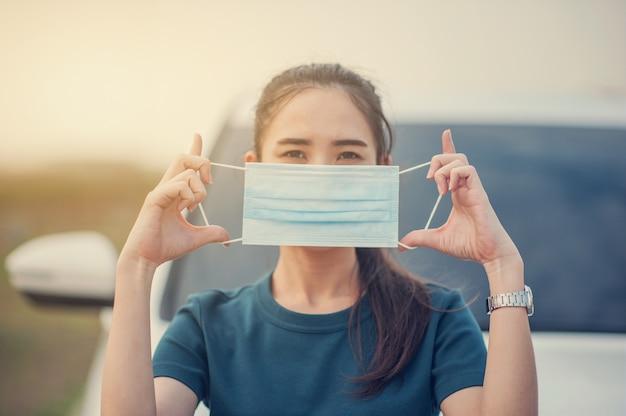 Aziatische vrouwen gebruiken een gezichtsmasker of een chirurgisch masker om het corona-virus of covid 19 te beschermen en thuis te blijven om thuis veilig op slot te blijven