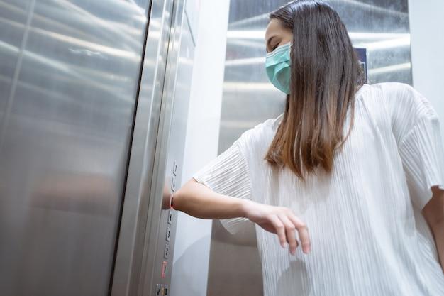 Aziatische vrouwen gebruiken ellebogen om de liftknop in te drukken om te voorkomen dat ze handen gebruiken.