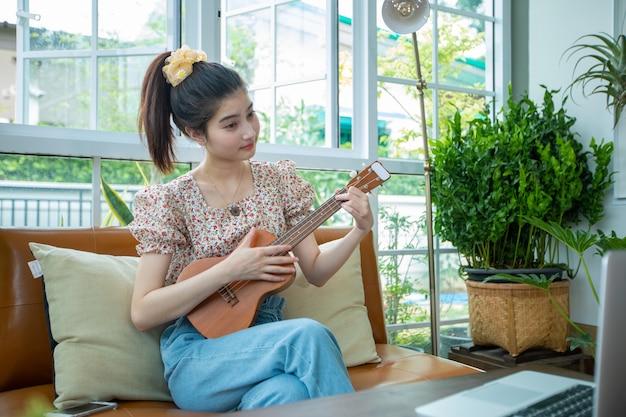 Aziatische vrouwen gebruiken hun notebooks om thuis het spelen van ukelele op internet te studeren en te oefenen.