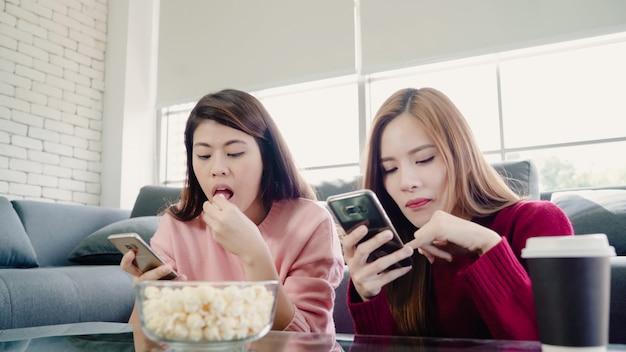 Aziatische vrouwen gebruikend smartphone en thuis eetend popcorn in woonkamer