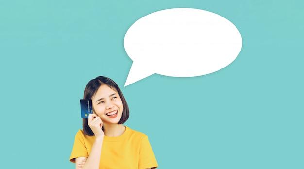 Aziatische vrouwen gele vrijetijdskleding die creditcard op lichtblauw houden