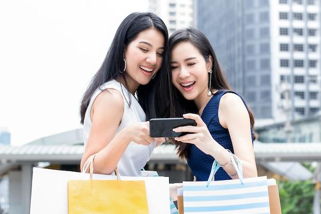Aziatische vrouwen genieten van online winkelen via smartphone tijdens het reizen in de stad