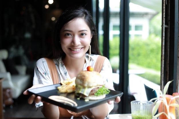 Aziatische vrouwen glimlachend en blij en genoten van het eten van hamburgers bij koffie en restaurant