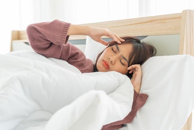 Aziatische vrouwen hoofdpijn en slapen op bed