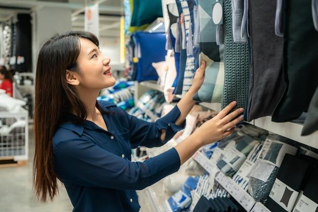 Aziatische vrouwen kiezen ervoor om nieuwe kussens in het winkelcentrum te kopen. winkelen voor boodschappen en huishoudelijke artikelen.