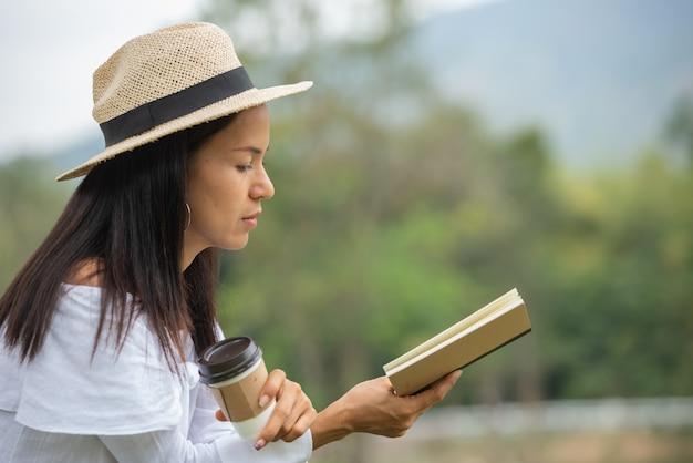Aziatische vrouwen lezen boeken en drinken koffie in het park.