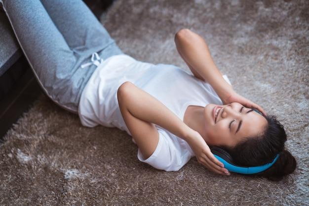 Aziatische vrouwen luisteren naar muziek en ze zingt in de kamer en slaapt vrolijk op het tapijt