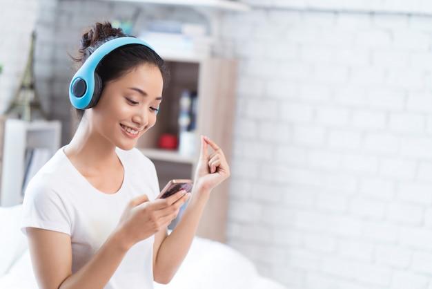 Aziatische vrouwen luisteren naar muziek en ze zingt vrolijk in de kamer