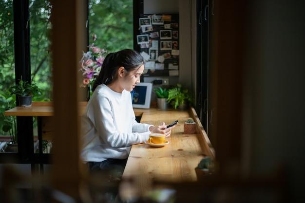 Aziatische vrouwen met behulp van het schrijven van berichten op een mobiele telefoon in koffie winkel