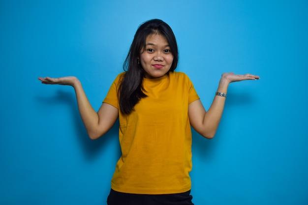 Aziatische vrouwen met een blauwe geïsoleerde achtergrond kijken naar de camera en maken een verward gebaar
