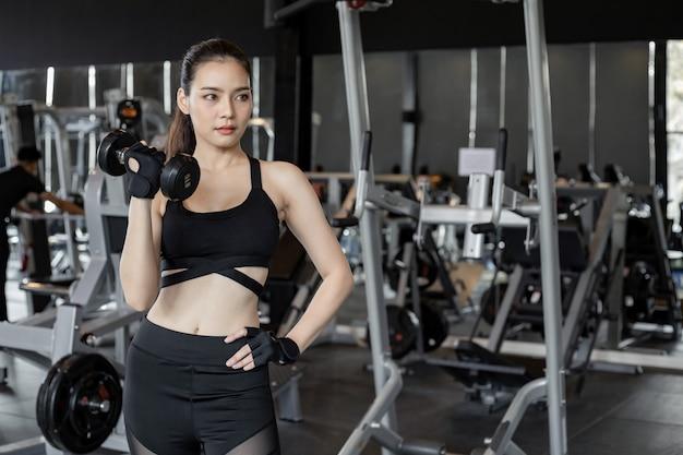 Aziatische vrouwen met halters in de sportschool.