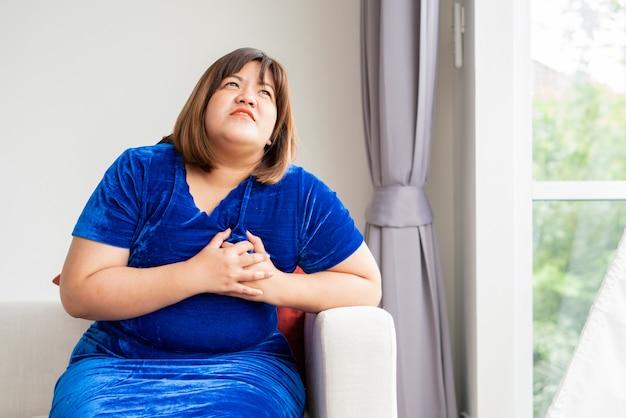 Aziatische vrouwen met overgewicht zitten op de bank in de woonkamer. en handgrepen in de borst vanwege hartaandoeningen