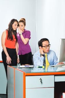 Aziatische vrouwen of werknemers kletsen of fluisteren over collega of man, die hem op kantoor pesten