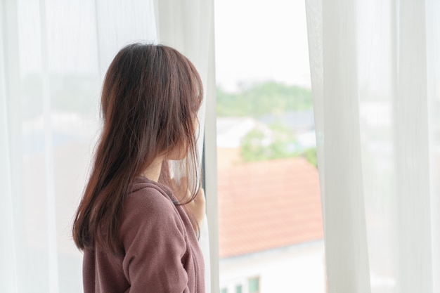 Aziatische vrouwen openen het gordijn in de ochtend