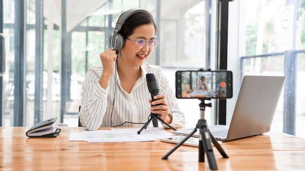 Aziatische vrouwen podcaster podcasting en opnemen van online talkshow in de studio met behulp van hoofdtelefoons, professionele microfoon en computerlaptop op tafel kijken naar camera voor radiopodcast.