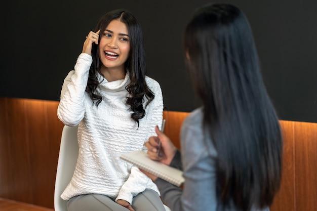 Aziatische vrouwen professionele psycholoog arts die het consult geeft aan vrouwelijke patiënten in livi