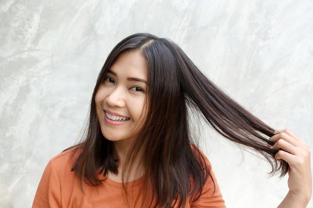 Aziatische vrouwen raken haar op grijze achtergrond.