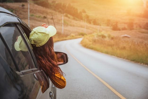 Aziatische vrouwen reizen in een auto die uit het raam kijkt.
