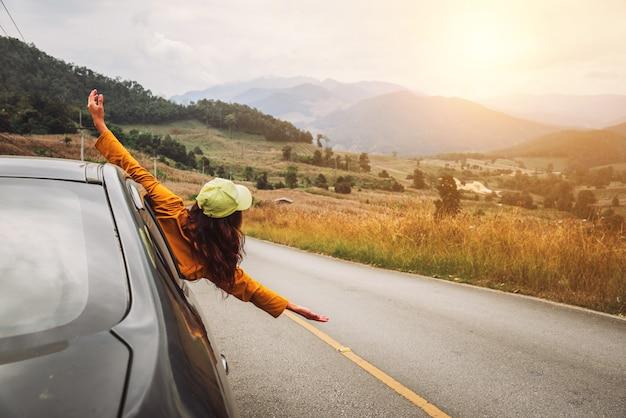 Aziatische vrouwen reizen in een auto met een half lichaam uit het raam.