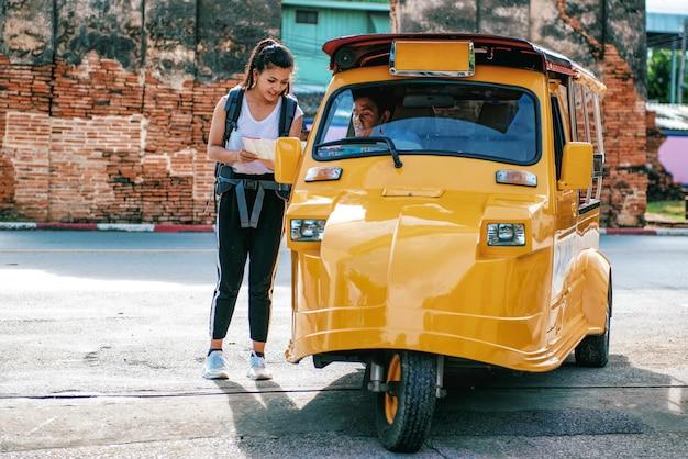 Aziatische vrouwen reizigers vragen tuk-tuk bestuurder over de juiste richting op de kaart tijdens het verkennen van reizen. bij het historische park thailand van ayutthaya.