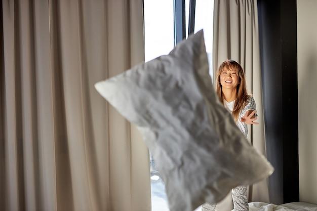 Aziatische vrouwen spelen 's ochtends met kussens, blij om te rusten, genieten alleen in het weekend, in pyjama staat ze op bed