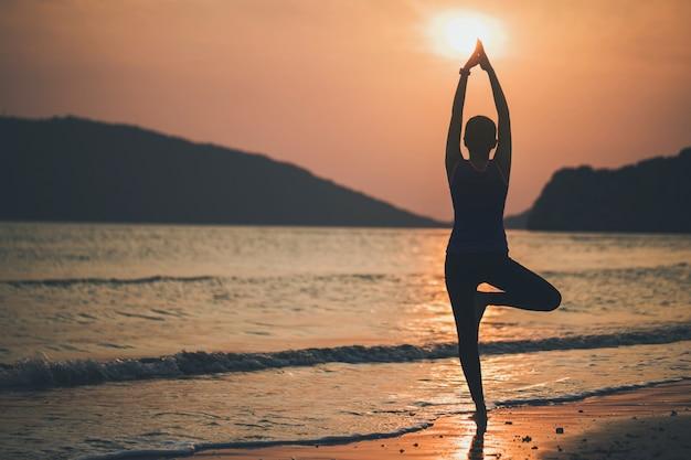 Aziatische vrouwen spelen yoga op een zandstrand bij de zee en de berg in de zonsopgangochtend. oefening en meditatie concept.