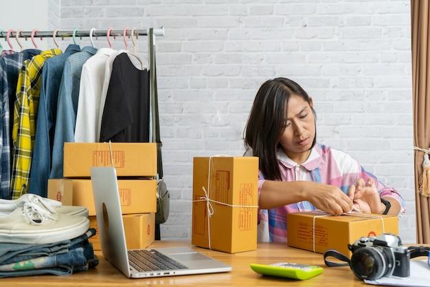 Aziatische vrouwen starten kartonnen doos met kleine bedrijfseigenaren inpakken