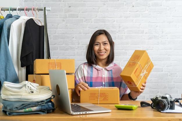 Aziatische vrouwen starten kleine kartonnen doos met verpakking van bedrijfseigenaar