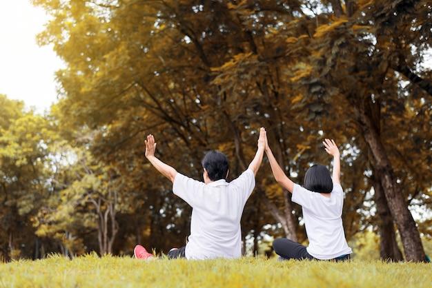 Aziatische vrouwen steken de hand op en ontspannen 's ochtends samen in het park, gelukkig en glimlachend, positief denken, gezond en lifestyle concept