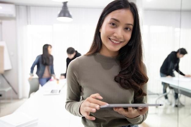 Aziatische vrouwen studenten glimlachen en tablet gebruiken het helpt ook om ideeën in het werk te delen