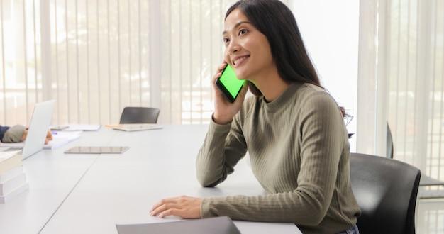 Aziatische vrouwen studenten lachen en hebben plezier en gebruiken slimme telefoon en tablet