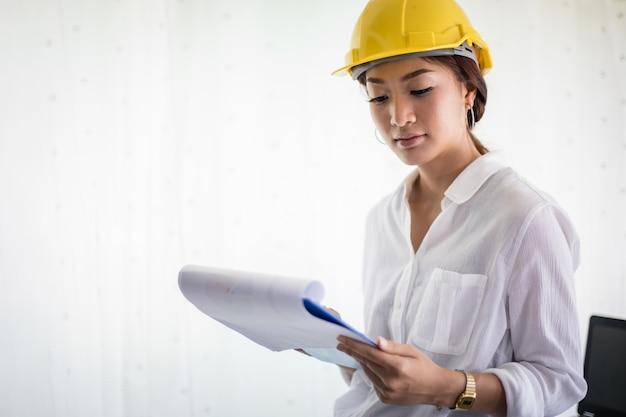 Aziatische vrouwen techniek inspecteren en werken en blauwdrukken houden op kantoor