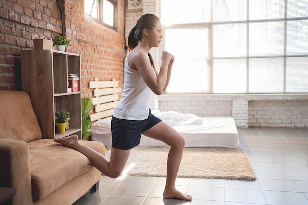 Aziatische vrouwen trainen 's ochtends in de slaapkamer, ze voelt zich verfrist en gedraagt zich als een hurkzit.