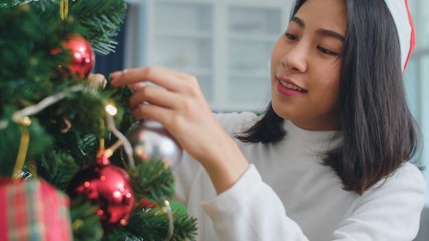 Aziatische vrouwen versieren kerstboom op kerstfestival. het vrouwelijke tiener gelukkige glimlachen viert thuis de vakantie van de kerstmiswinter in woonkamer. close-up shot.