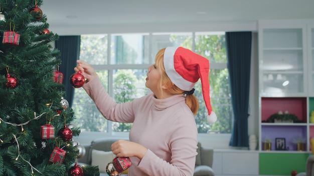 Aziatische vrouwen versieren kerstboom op kerstfestival. het vrouwelijke tiener gelukkige glimlachen viert thuis de vakantie van de kerstmiswinter in woonkamer.