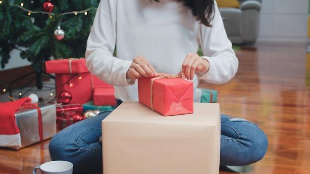 Aziatische vrouwen vieren kerstfestival. de vrouwelijke sweater van de tienerslijtage en de kerstmishoed ontspannen gelukkige verpakkende giften dichtbij kerstboom genieten samen thuis van de vakantie van de kerstmiswinter in woonkamer.