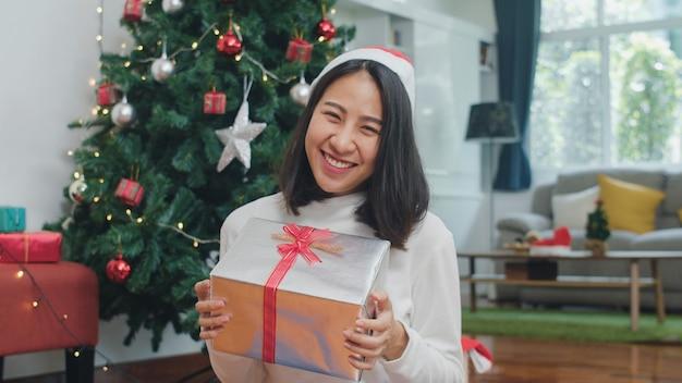 Aziatische vrouwen vieren kerstfestival. de vrouwelijke sweater van de tienerslijtage en kerstmishoed ontspant gelukkige greepgift glimlachend dichtbij kerstboom geniet thuis van de vakantie van de kerstmiswinter in woonkamer.